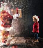 Santa Claus livrent un cadeau à un enfant photo libre de droits