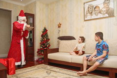Santa Claus in a long bright suit and gloves gets gifts from the big red bag - Russia, Moscow, 07 December, 2016 Royalty Free Stock Photo