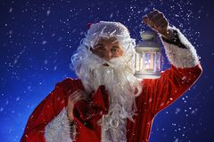 Santa Claus with a long white beard holds candle holder with burning candle against a snowing blue sky. Christmas stock photo