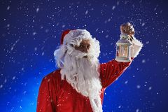 Santa Claus with a long white beard holds a lamp with a candle against a blue sky. It is snowing. Christmas stock image
