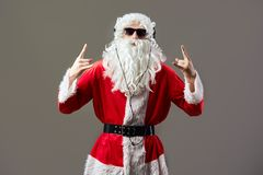 Santa Claus with a long white beard in sunglasses and headphones shows a rock sing on the gray background. royalty free stock photography