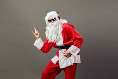 Santa Claus with a long white beard in sunglasses and headphones shows a rock sing on the gray background. stock images
