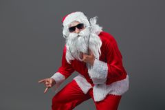 Santa Claus with a long white beard in sunglasses and headphones stands shows a rock sing on the white background. stock photography