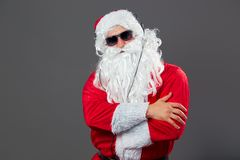 Santa Claus with a long white beard and in sunglasses and headphones stands on the white background. stock photo