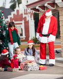 Santa Claus Looking At Children Opening Gifts Stock Photos