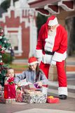 Santa Claus Looking At Children Opening jul Arkivbild