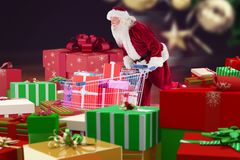 Santa claus looking for gift boxes to fill in the shopping cart. Against christmas decoration Royalty Free Stock Images