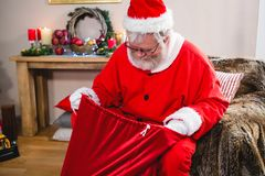 Santa claus looking in his gift sack Stock Photo