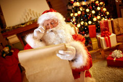 Santa Claus looking at long list with children desire. For Christmas gift royalty free stock photo