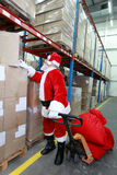 Santa claus looking for presents in storehouse. Santa claus with pallet jack, reading label on large box in storehouse Royalty Free Stock Photos