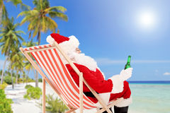 Santa Claus lying on a chair and drinking beer, on a beach Stock Image