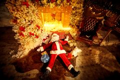 Santa Claus is lying drunk on the floor by the fireplace after C. Santa Claus is lying drunk tired on the floor by the fireplace after Christmas royalty free stock photo