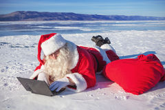 Santa Claus lying on the snow, looking at laptop n Royalty Free Stock Photo