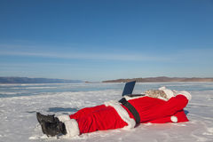 Santa Claus lying on the snow, looking at laptop news Stock Photography