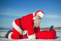 Santa Claus lying on the snow, looking at laptop news Royalty Free Stock Images