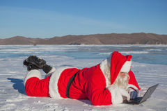 Santa Claus lying on the snow, looking at laptop news Stock Photo