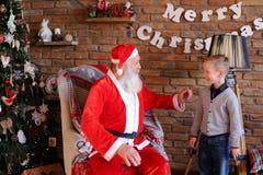Santa Claus mágica e o rapaz pequeno que enganam ao redor e têm o tog do divertimento Imagens de Stock