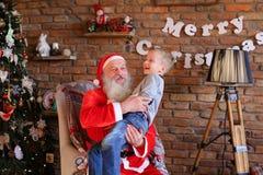 Santa Claus mágica e o rapaz pequeno que enganam ao redor e têm o tog do divertimento Fotos de Stock Royalty Free