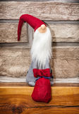 Santa claus made of cloth with gifts is sitting over the stone f. Ireplace. Christmas decoration Stock Photography