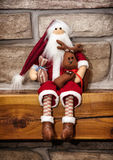 Santa claus made of cloth is sitting with reindeer over the ston Stock Photography