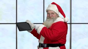 Santa Claus with magic computer tablet. Father Christmas giving thumb up. Christmas, advertisement, technology and people concept stock video footage