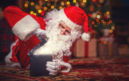Santa Claus with magical glowing Christmas present gift Stock Photos