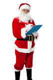 Santa Claus making list of gift recipients. And smiling at the camera Stock Photography