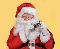 Santa Claus making photo over yellow background Royalty Free Stock Photo