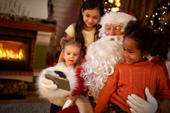 Santa Claus making selfie with three girls Royalty Free Stock Photos