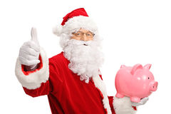 Santa claus making a thumb up sign and holding a piggybank. Isolated on white background Royalty Free Stock Image
