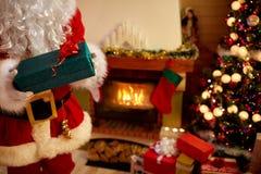 Santa Claus in mani gloved che tengono il contenitore di regalo Fotografie Stock