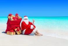 Santa Claus manuseia acima de gesticular com saco do Natal completamente de caixas de presente envolvidas Imagem de Stock