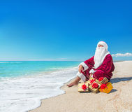 Santa Claus with many golden gifts relaxing at beach  - christma Royalty Free Stock Photography