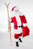 Santa Claus marchant avec le sac et les skis en bois Photographie stock
