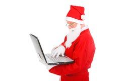Santa Claus med bärbar dator Arkivbilder