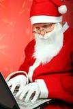 Santa Claus med bärbar dator Royaltyfria Foton