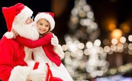 Santa Claus med den lyckliga flickan över julträd arkivfoto