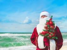 Santa Claus med det dekorerade julträdet på den tropiska havsstranden Arkivbild