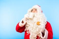 Santa Claus med en kopp kaffe eller ett te och ett kex på blåa lodisar royaltyfria bilder