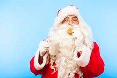 Santa Claus med en kopp kaffe eller ett te och ett kex på blåa lodisar arkivbilder