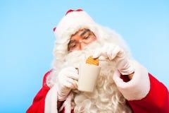 Santa Claus med en kopp kaffe eller ett te och ett kex på blåa lodisar royaltyfri bild