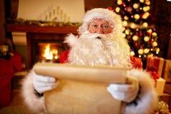 Santa Claus med en lista av barnönska Fotografering för Bildbyråer