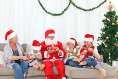 Santa Claus med en lycklig familj Arkivfoto