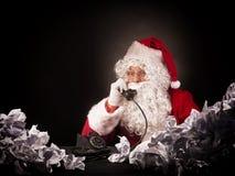 Santa Claus med en stor hög av skrynklig legitimationshandlingar Fotografering för Bildbyråer