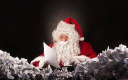 Santa Claus med en stor hög av skrynklig legitimationshandlingar Royaltyfri Fotografi