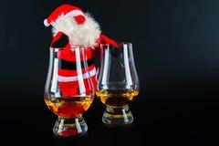 Santa Claus med enkelt exponeringsglas för maltwhisky, symbol av jul Arkivbild