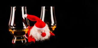 Santa Claus med enkelt exponeringsglas för maltwhisky, symbol av jul arkivfoto