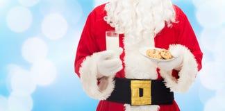 Santa Claus med exponeringsglas av mjölkar och kakor Royaltyfri Foto
