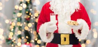 Santa Claus med exponeringsglas av mjölkar och kakor royaltyfria bilder