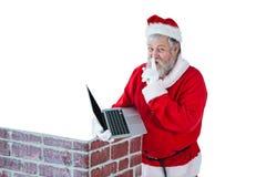 Santa Claus med fingret på kanter, medan genom att använda bärbara datorn mot vit bakgrund Arkivfoto